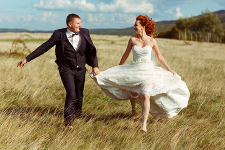 Bride and groom look funny walking on the field in a windy weather Stock Photo
