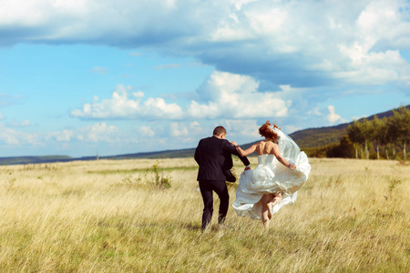 Bride jumps up walking behind a groom acroos a golden field Stock Photo
