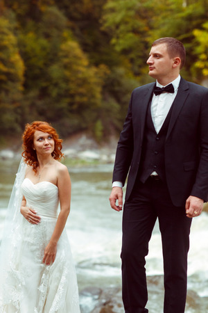 Groom stands on a stone behind a mountain river while bride admires him from beneath