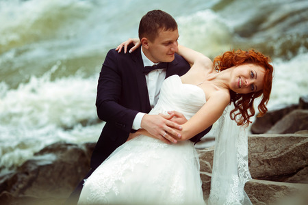 lejos: El novio dobla a la novia sentada en las piedras detrás de un río de montaña
