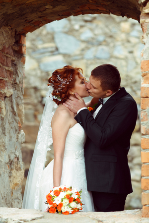 passionate kiss: A passionate kiss of newlyweds standing in big brick window Stock Photo