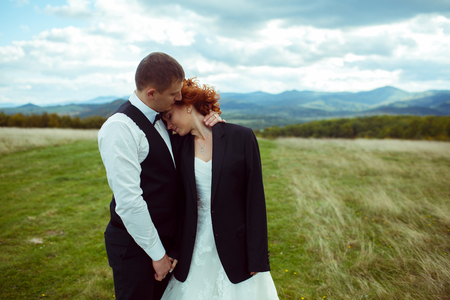 Groom holds brides neck tenderly standing on the field in windy weather