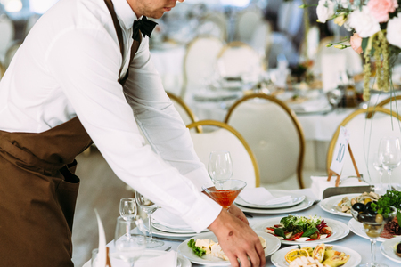 Waiter puts a plate with food on the table Stock Photo