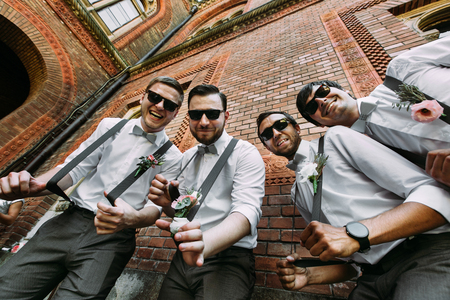 Funny groomsmen in the sunglasses and bow-ties