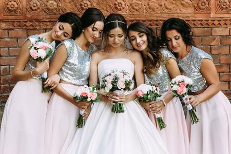 Nette Brautjungfern in den stilvollen Kleidern und eine Braut