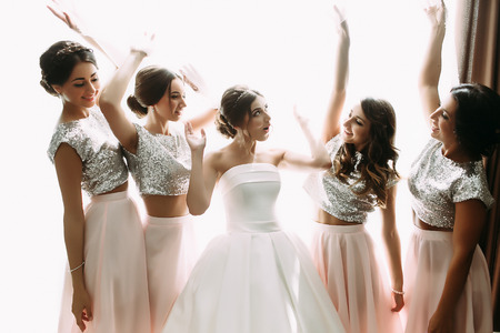 Funny photo of the bride and bridesmaids in the room