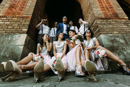 Bridesmaids and groomsmen with a groom in the arch