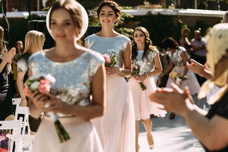 Glamorous bridesmaids are walking on the wedding ceremony Stockfoto