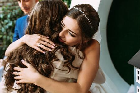 花嫁が結婚式に彼女の友人を抱きしめています。