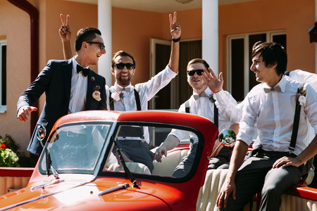 Boys in the sunglasses in the old red car