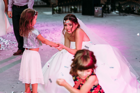 Cheerful bride with the little girl on the wedding