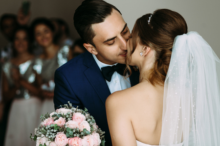 embracement: Romantic and tender kiss of the bride and groom