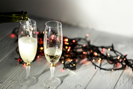 debt goals: Cold champagne flutes stand on wooden floor behind Christmas garland