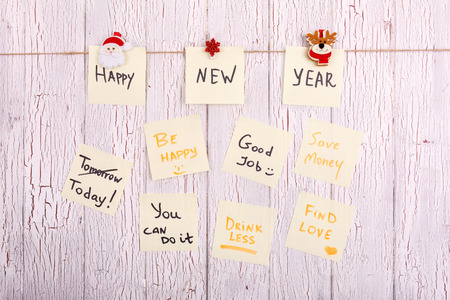 Cards with words Happy New Year,  Today, Be happy, Good job, Save money, Drink less, You can do it lie on wooden table
