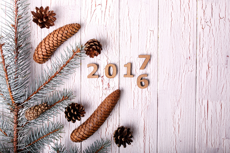 debt goals: Conifer cones lie on white wooden table with wooden numbers 2017 and 2016