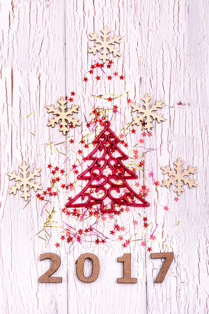 Christmas tree made of ribbons and wooden snowflakes lies on white table over wooden number 2017