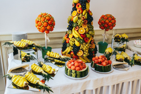 receptions: Ananases, grape, apples, oranges and other exotic fruits stand on a buffet