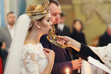 Bride kisses a crown held by a priest