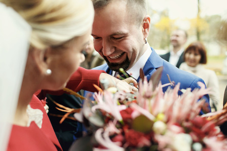 Groom laughs while bride adjusts a veil on his jacket