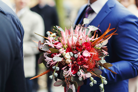 Perfect red bouqet made of autumn flowers held by a man in blue suit