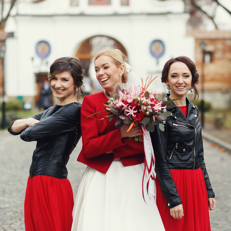 Bride and bridesmaids in leather jacket lean back to back posing in the park