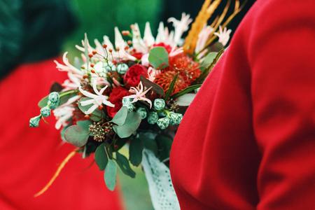 Wedding bouquet made of roses and ranunculus is held by a lady in red