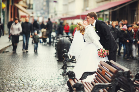 crowded street: Groom kisses brides neck standing between benches on a crowded street Stock Photo