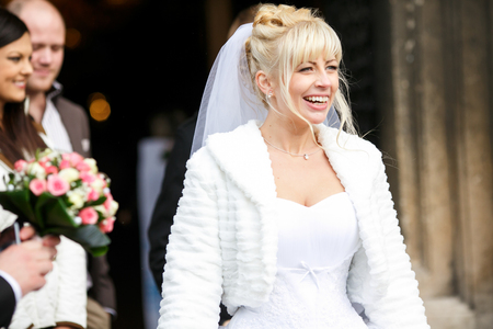 sincerely: Bride smiles sincerely walking out of the church Stock Photo