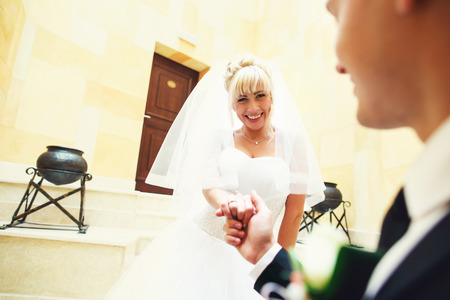 Bride smiles going downstairs, holding grooms arm