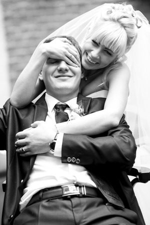 Groom sits on a chair while bride closes his eyes with her arm standing behind him