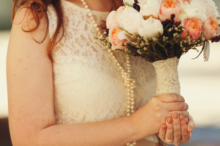 Bride in pearls holds a wedding bouquet decotated with lace Stock Photo