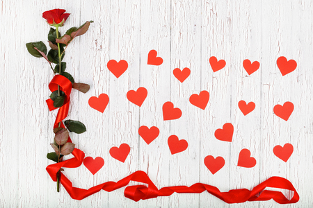 Red rose and paper hearts lie on white wooden table