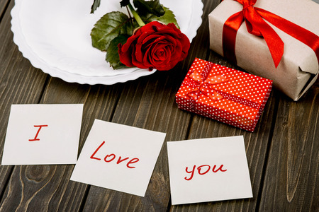 atmospheric: plate with red rose and gift boxes lie on wooden surface