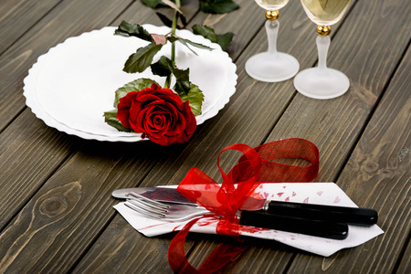 plate with red rose and cutlery with napkin lie on wooden surface