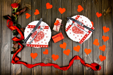 White plates with red serviettes, forks and knives stand among paper hearts before red rose
