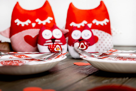 plates with cutlery and soft red owls lie on wooden surface Stock Photo