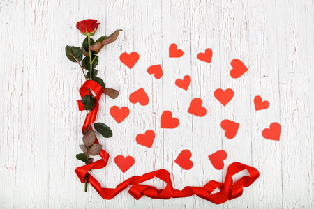 Red rose with long red silk ribbon surrounded with paper hearts lies on white wooden floor Stock Photo