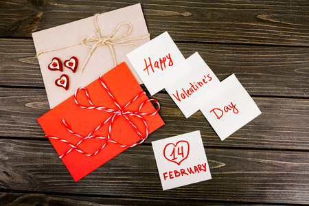 leaflets: white leaflets and red envelope lying on wooden surface Stock Photo