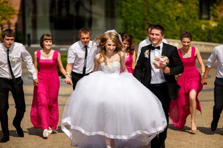 Bruid en bruidegom lopen in het park, gevolgd door hun vrienden