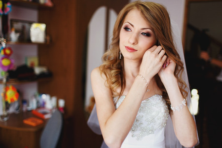 jewerly: Bride with stunning make-up adjusts her jewerly in a room