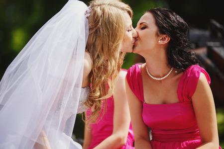 Mariée embrasse les lèvres d'une demoiselle d'honneur en robe rose