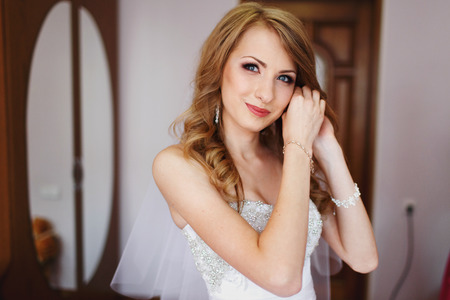jewerly: Bride smiles tender while putting on jewerly