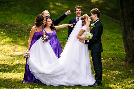 reach out: Friends reach out their fingers at newlyweds while they kiss Stock Photo