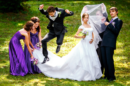 Groom jumps over bride's dress while bridesmaids hold it and groomsmen play with a veil Stockfoto