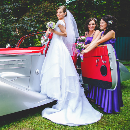Bride stands on a doorstep of an old vintage car while bridesmaids wait behind her