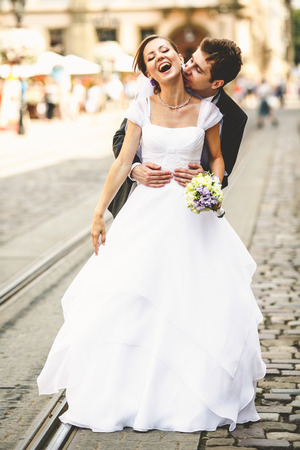 Bride laughs while groom kisses her neck somewhere in the old town