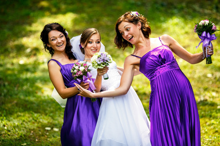 bend over: Gracious bride and bridesmaids tries to bend over standing on the field Stock Photo