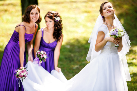 Bridesmaids grimace standing behind a pretty bride Stock Photo