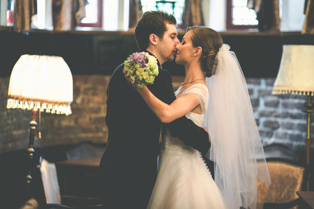 Newlyweds dance in a vintage hall kissing tenderly