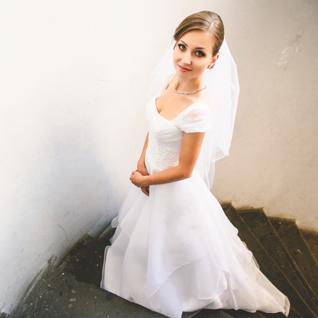 Bride looks shy posing on the stone stairs Stock Photo
